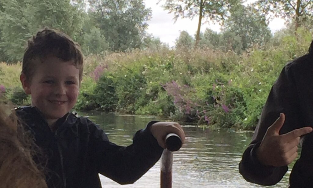 Boy helping to drive a narrow boat on the river Chelmer