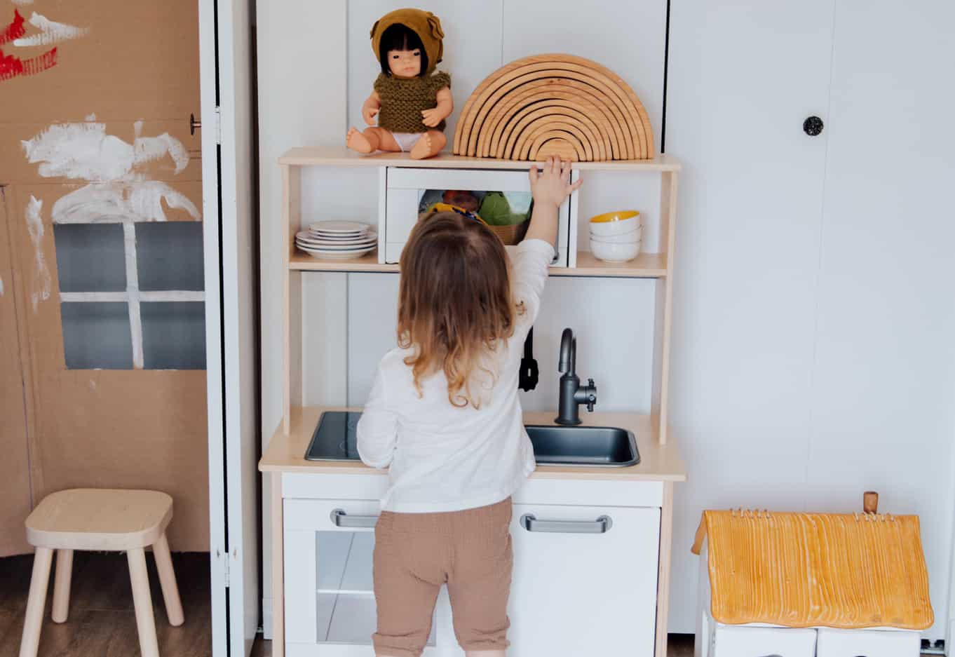 Child using a play kitchen at nursery